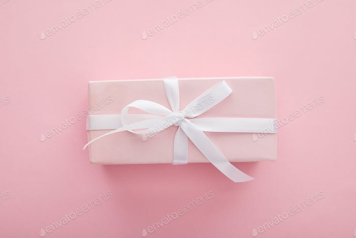 Top View of Pink Gift With White Ribbon on Pink Background