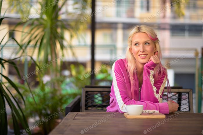 Happy young beautiful blonde woman thinking at the coffee shop