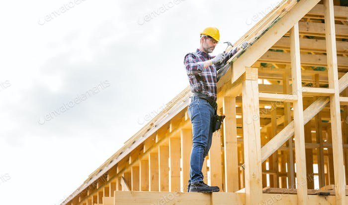 Roofer builder working on roof structure at construction site