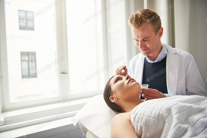 Cosmetologist applying facial mask on woman face