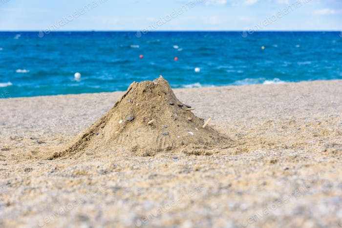 Volcano made from sand on the beach