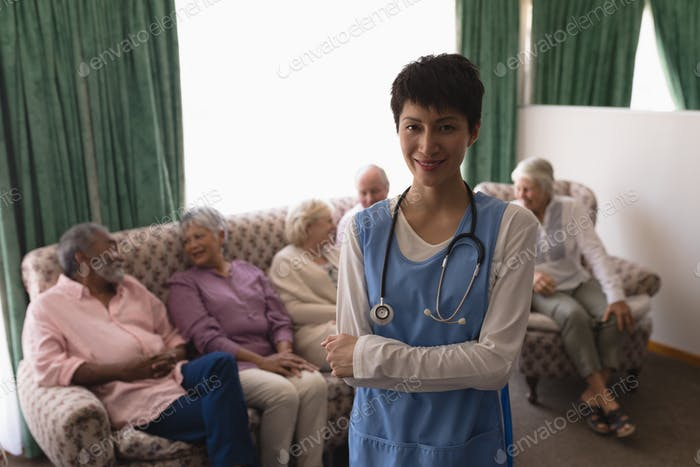 Female doctor standing with arms crossed with senior person behind her on the sofa