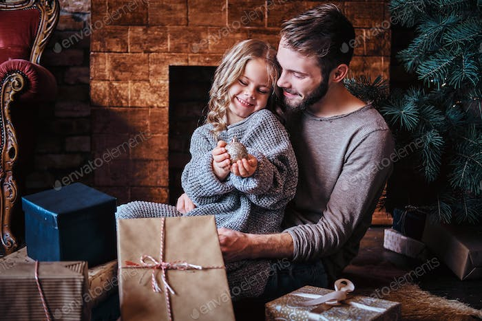Happiness father and his cute little daughter sitting on the floor surrounded by gifts