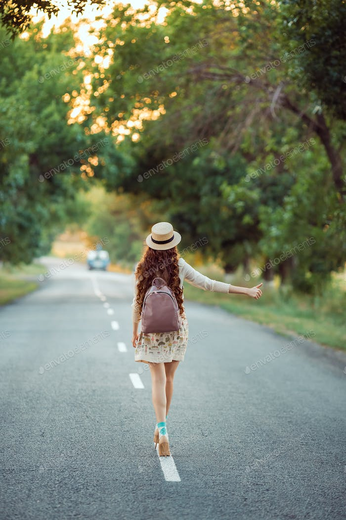 Girl With Hat and Backpack Hitchhiking on the Road