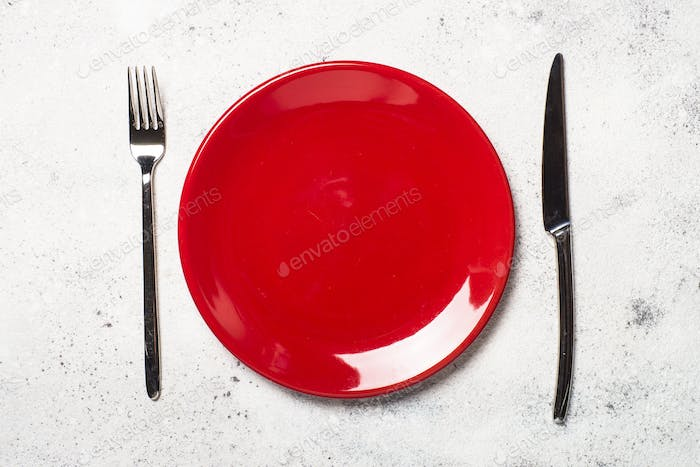 Red plate and cutlery  on light stone tabl