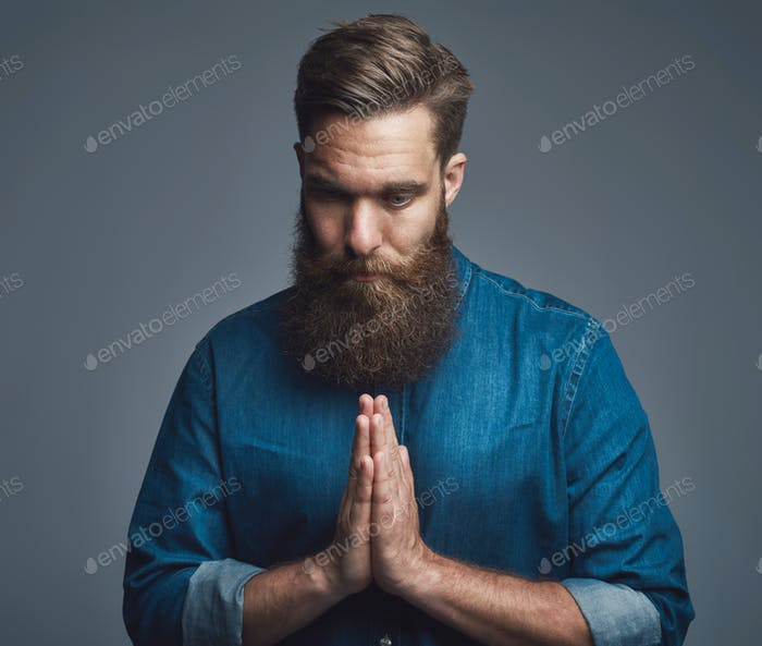 Bearded young man praying against a gray background