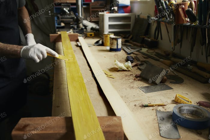 A man examining a piece of wood at a workbench.