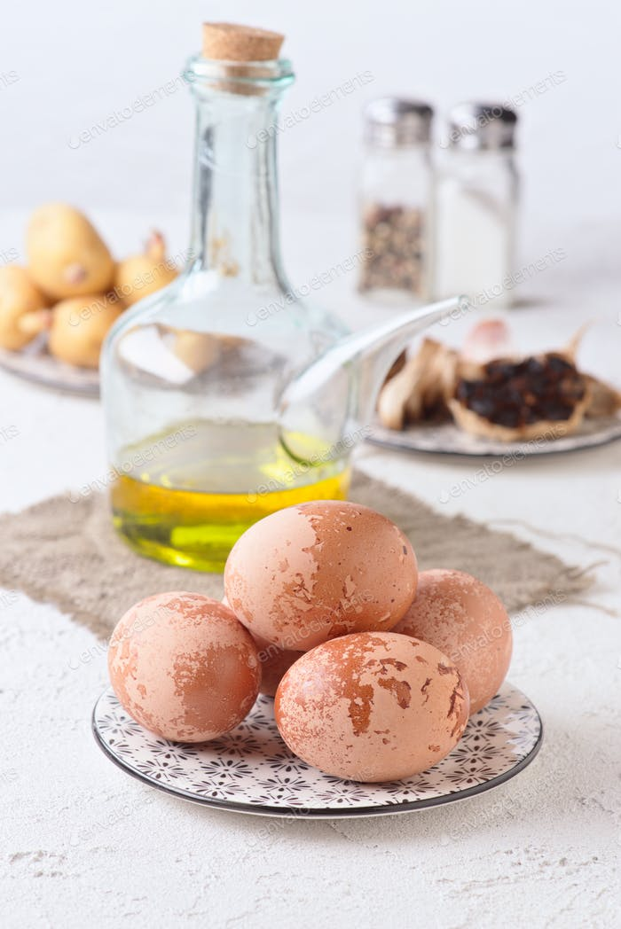 Black garlic oil eggs and other cooking ingredients on textured white base