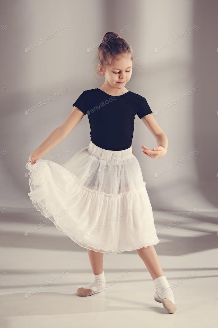 Die kleine Balerina Tänzerin auf grauem Hintergrund