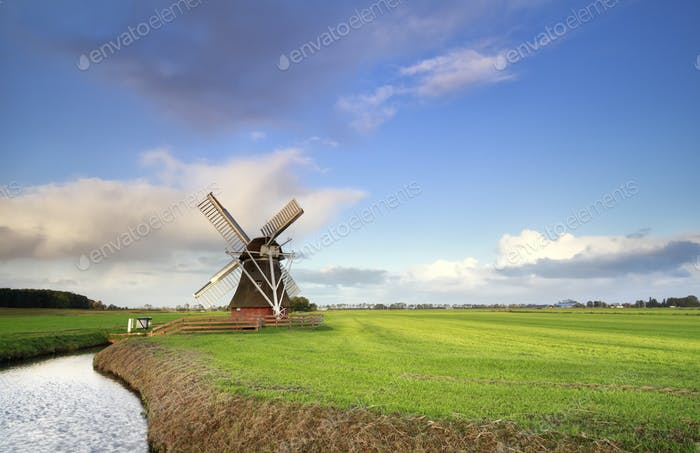 Dutch windmill on green meadow by river