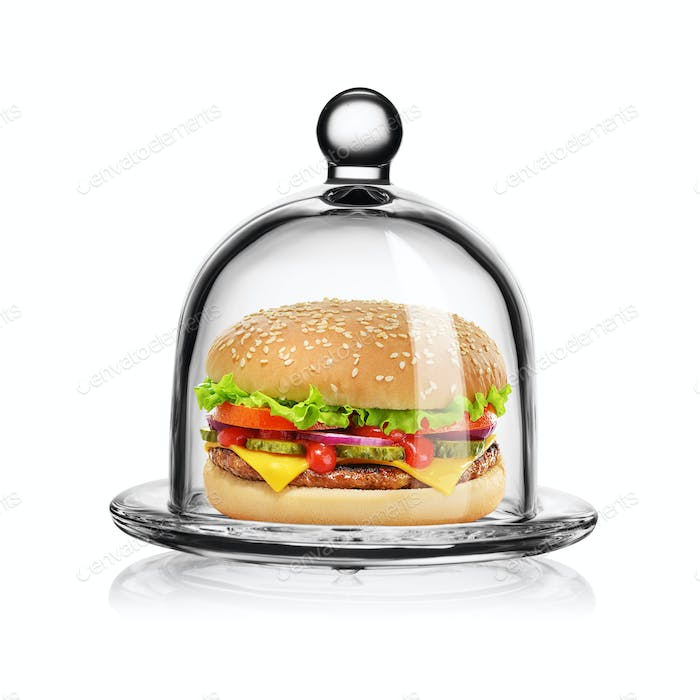 Classic cheeseburger in glass bell jar isolated on white.