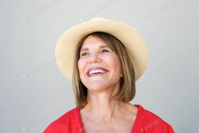 beautiful older woman laughing with hat against gray wall