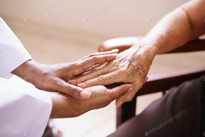 Senior Frau im Gespräch mit schwarz Arzt in Hospiz