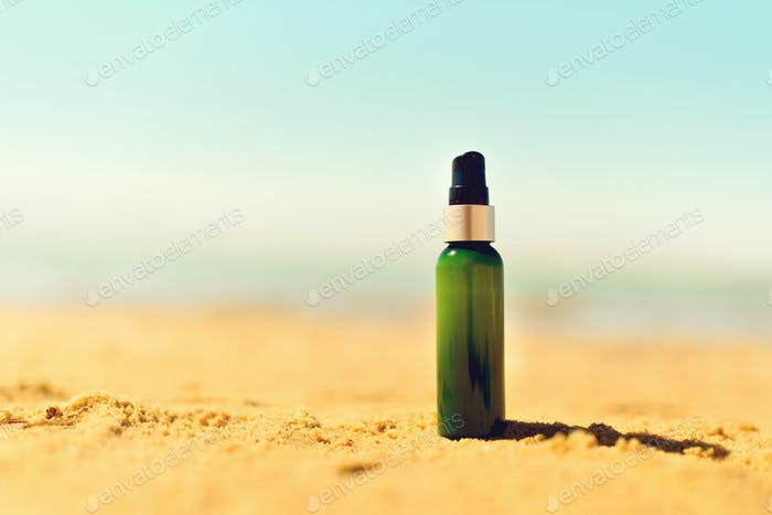 Bottle of sunscreen in sand against sea background with copyspace. Vacation and travel wallpaper