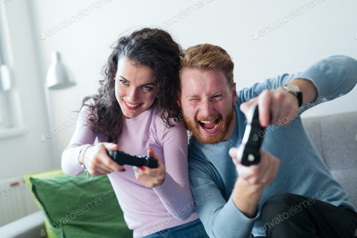 Young couple having fun playing video games