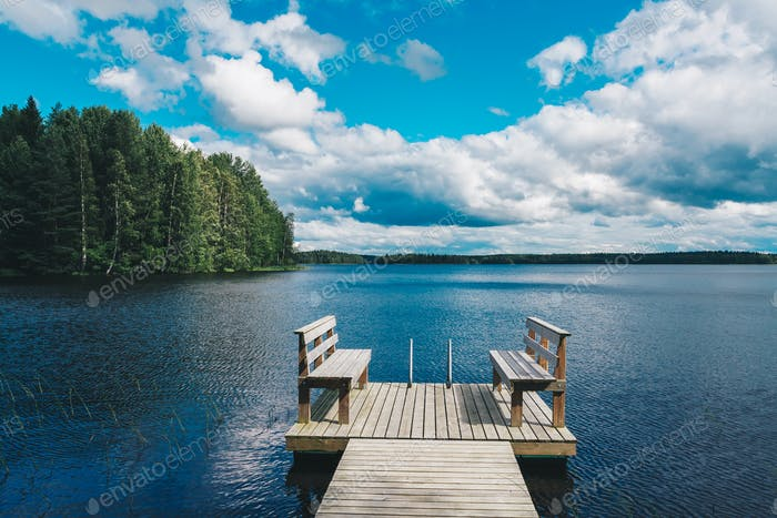 Two wooden chairs bench on a wood pier overlooking a blue lake water with green forest and cloud sky