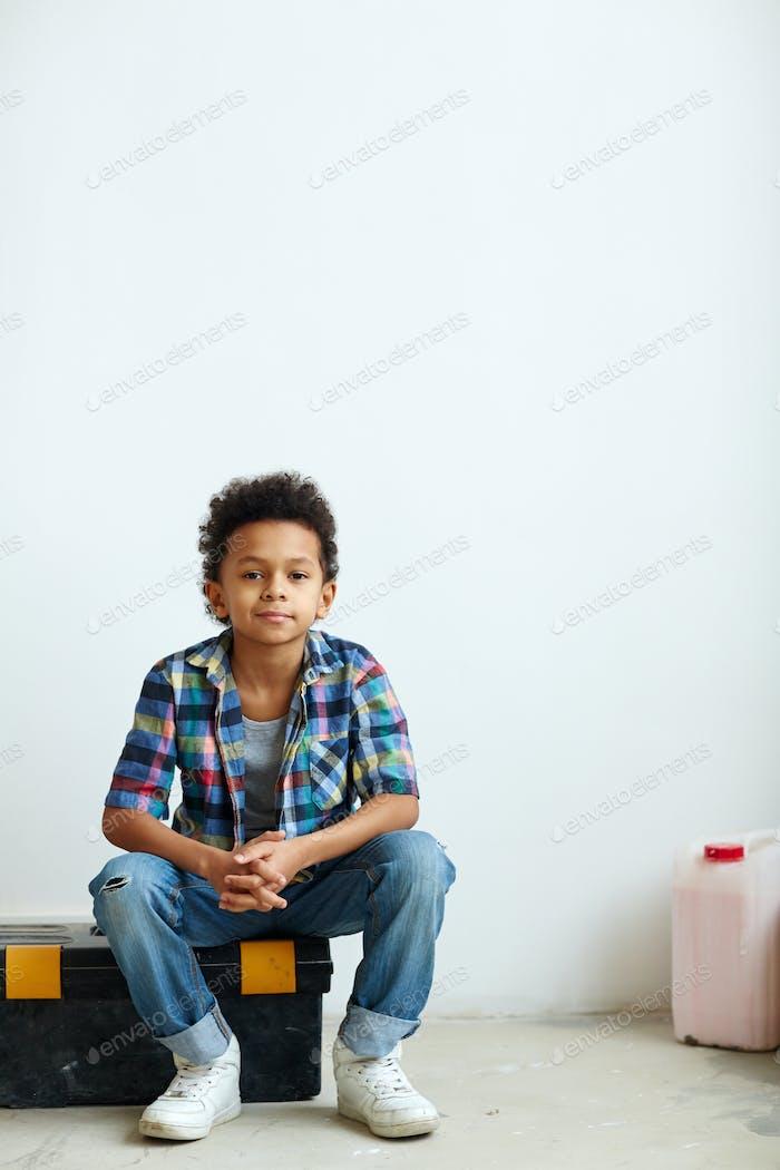 Junge auf Werkzeugkasten