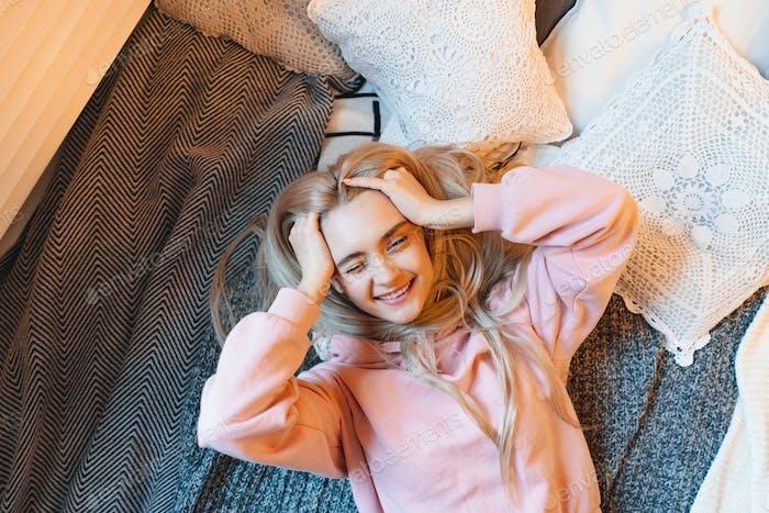 Chica sonriente, con el pelo rubio largo, disfrutando de la felicidad mientras lyi