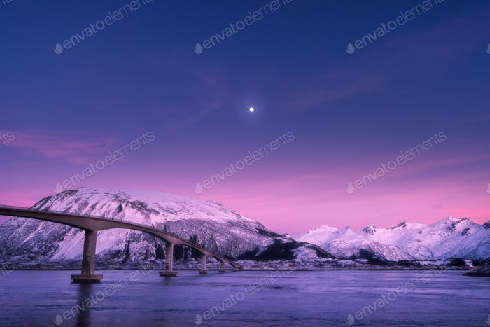 Bridge against snowy mountains, purple sky with pink clouds and moon