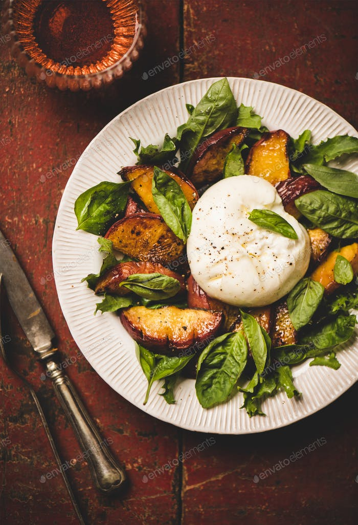 Salad with burrata cheese and peaches and rose wine, close-up