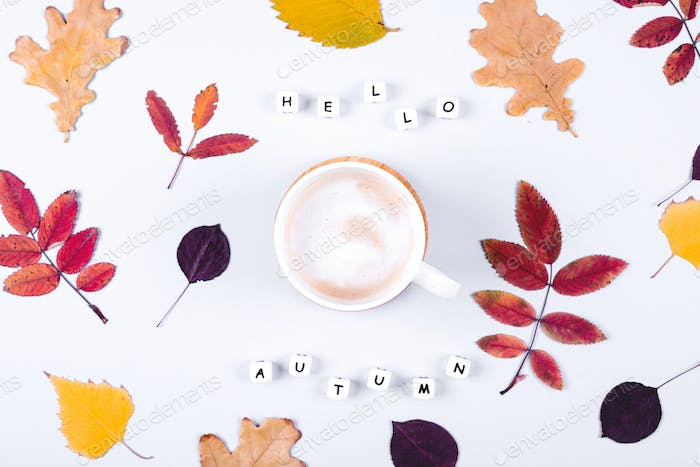 Letters words Hello Autumn and cup of coffee on grey background. Colorful autumn leaf. Flat lay