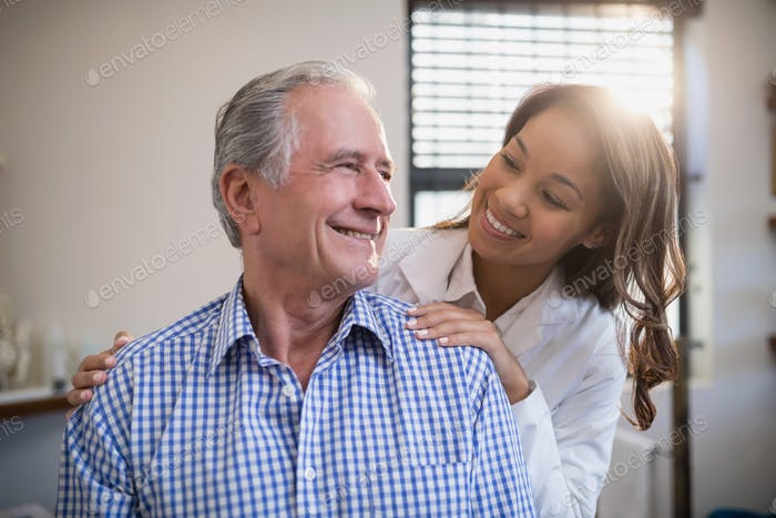 Smiling therapist and male patient looking at each other