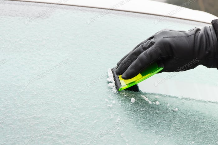 Hand in glove scraping ice from car windscreen