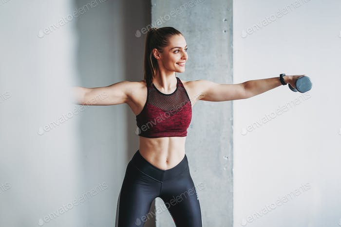 Attractive fit young woman in sport wear smiling girl trains with dumbbells