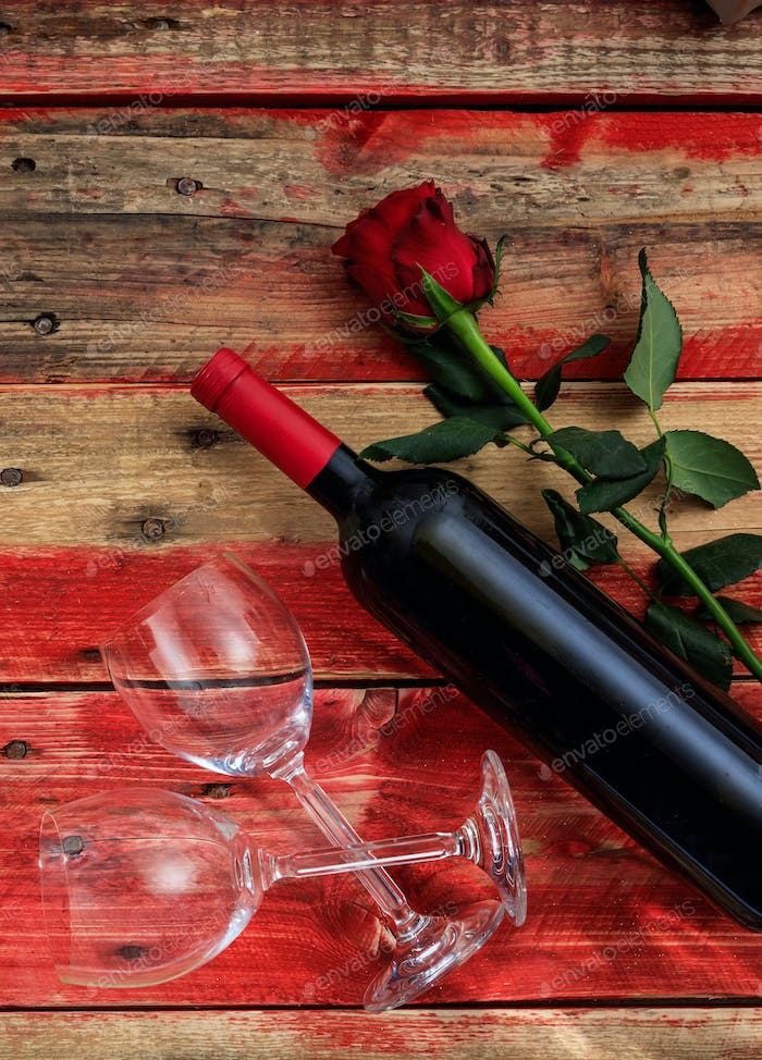 Valentines day. Red wine bottle, glasses and a rose on red wooden background