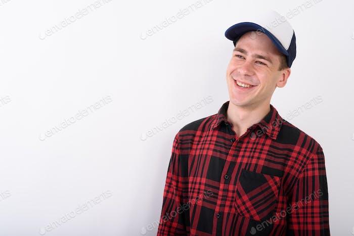 Hombre joven guapo que lleva gorra de béisbol y camisa roja a cuadros
