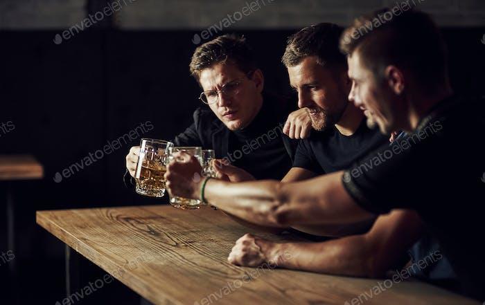 Drei Sportfans in einer Bar beobachten Fußball. Mit Bier in den Händen