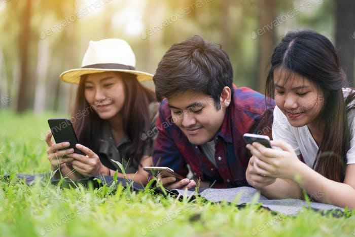 A group of young people using mobile phone while lying down in the park
