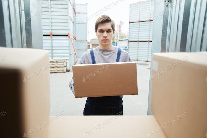 Junger Arbeiter Putting Box in Behälter