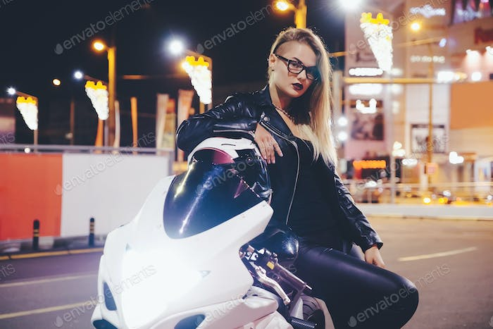 Portrait woman biker enjoying night city life and lights sitting