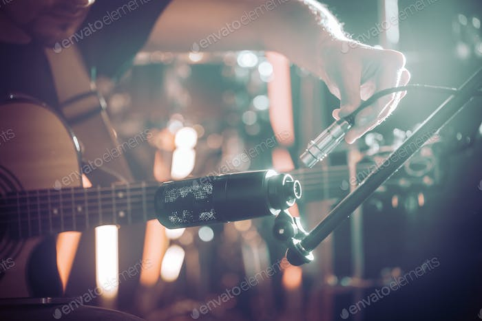 The musician connects the microphone to record an acoustic guitar close-up.