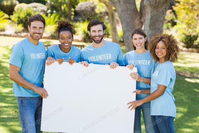 Retrato de grupo voluntario sosteniendo hoja en blanco