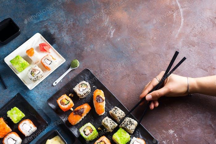 Verschiedene frische und leckere Sushi Set auf weißem Schiefer, Hand mit Schieferstäbchen, Sauce auf hellem Stein