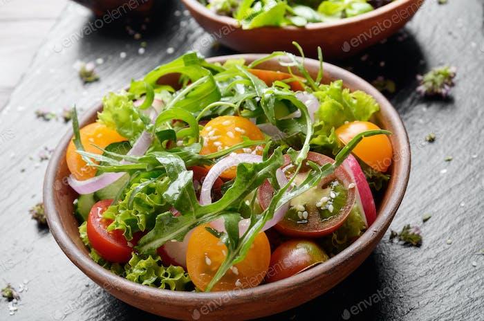 Vegetable salad of lettuce, cherry tomatoes, radish, cucumber, onion and basil on slate tray