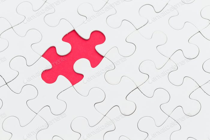 Puzzle with missing piece over red background