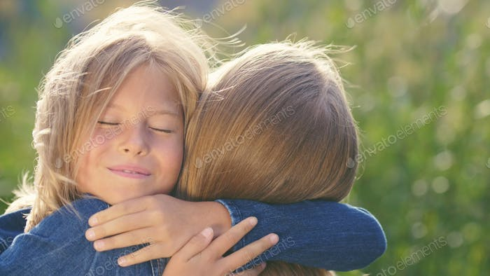 Hugging mother and daughter in summer
