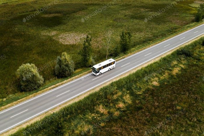 Aerial view of passenger bus on road through countryside