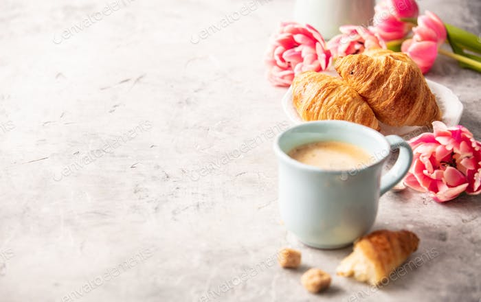 Morning coffee, croissants and spring tulips on light grey backg