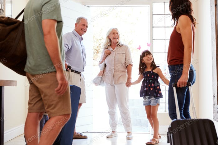 Three generation white family at front door preparing to leave home to go on holiday, close up, crop