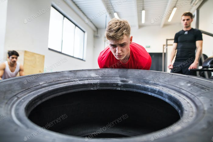 Fit young man with friends in gym working out, moving tire.