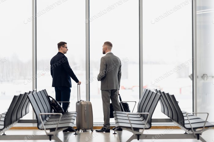 Silhouette of two businessman standing in front of a big window at airport at wating area near