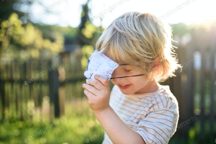 Kleiner Junge mit Gesichtsmaske spielt im Freien, Coronavirus Konzept