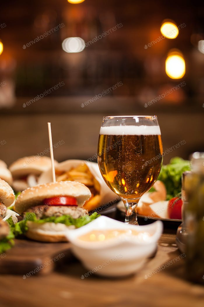Golden beer next to delicious burgers on wooden table