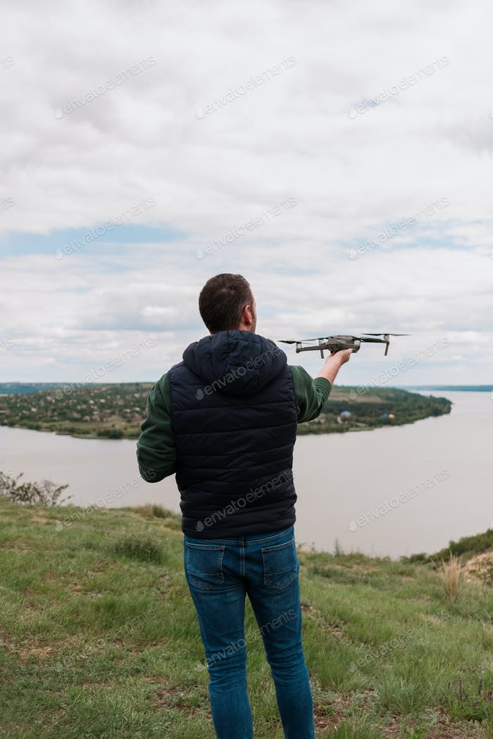Young man piloting a drone in nature