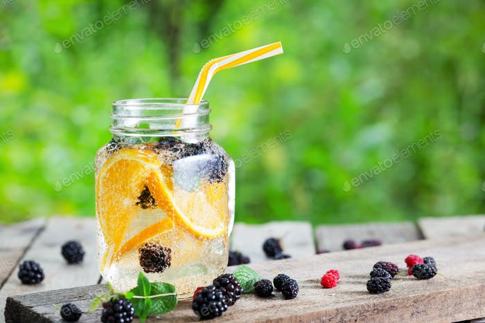 Cocktail lemonade from orange and berries in mason jar