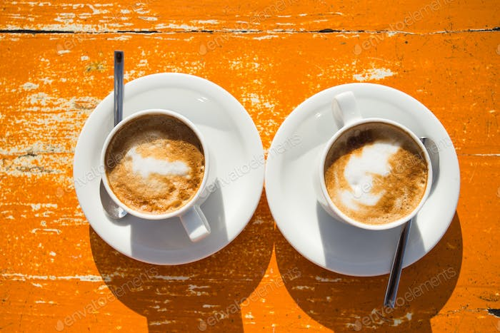 Two invigorating cappuccinos on the table await you, top view